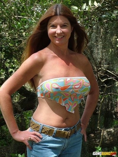 Middle aged lady Dee Delmar gets naked for nude posing underneath a tree