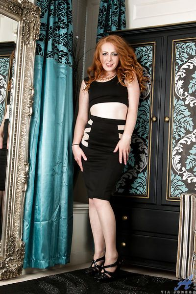 Mature redhead babe Tia Jones spreading stocking clad legs in high heels