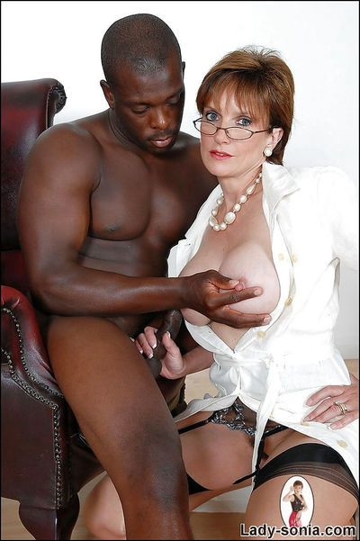 Bosomy mature slut in stockings jerking off a black prick