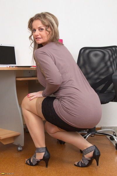 Mature business woman strips down to tan stockings to pose nude in home office