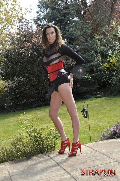 A clothed Strapon Jane flaunts her strapon cock in garden wearing see thru top
