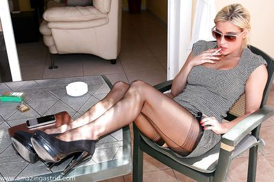 Fully clothed blonde in sunglasses and stockings having a smoke outdoors