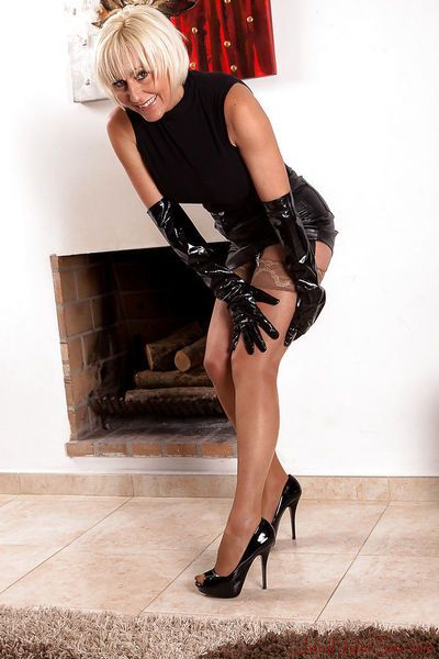 Short haired older dame Jan Burton posing solo in long black latex gloves