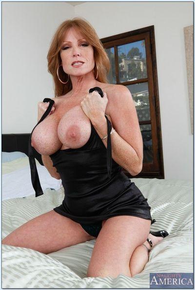 Horny mature Darla Crane in high heels shows her big tits.