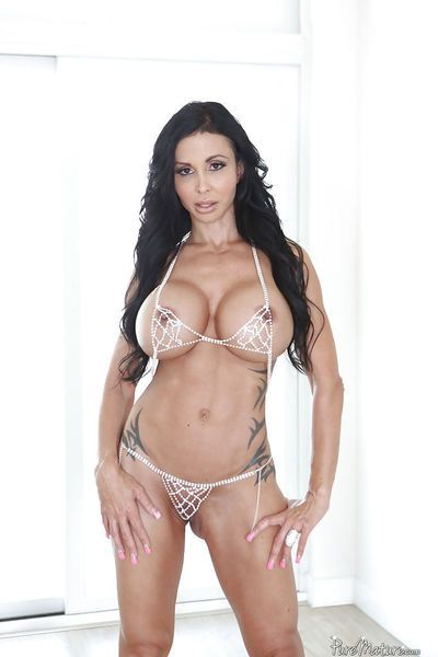 Tattooed mature brunette Jewels Jade unveiling huge hooters in high heels