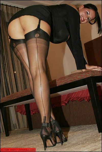 Seductive mommy with amazing hooters posing solo in stockings and lingerie