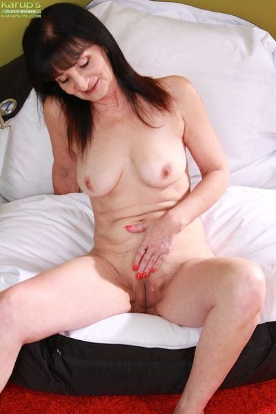 Barefoot mature lady Ginger Kovra baring big tits and pussy while stripping