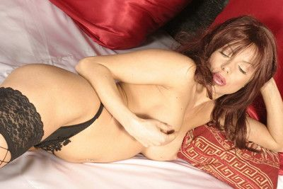 Milf redhead posing in stockings on the bed