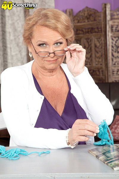 Non nude mature woman in glasses knits herself a skimpy bikini top