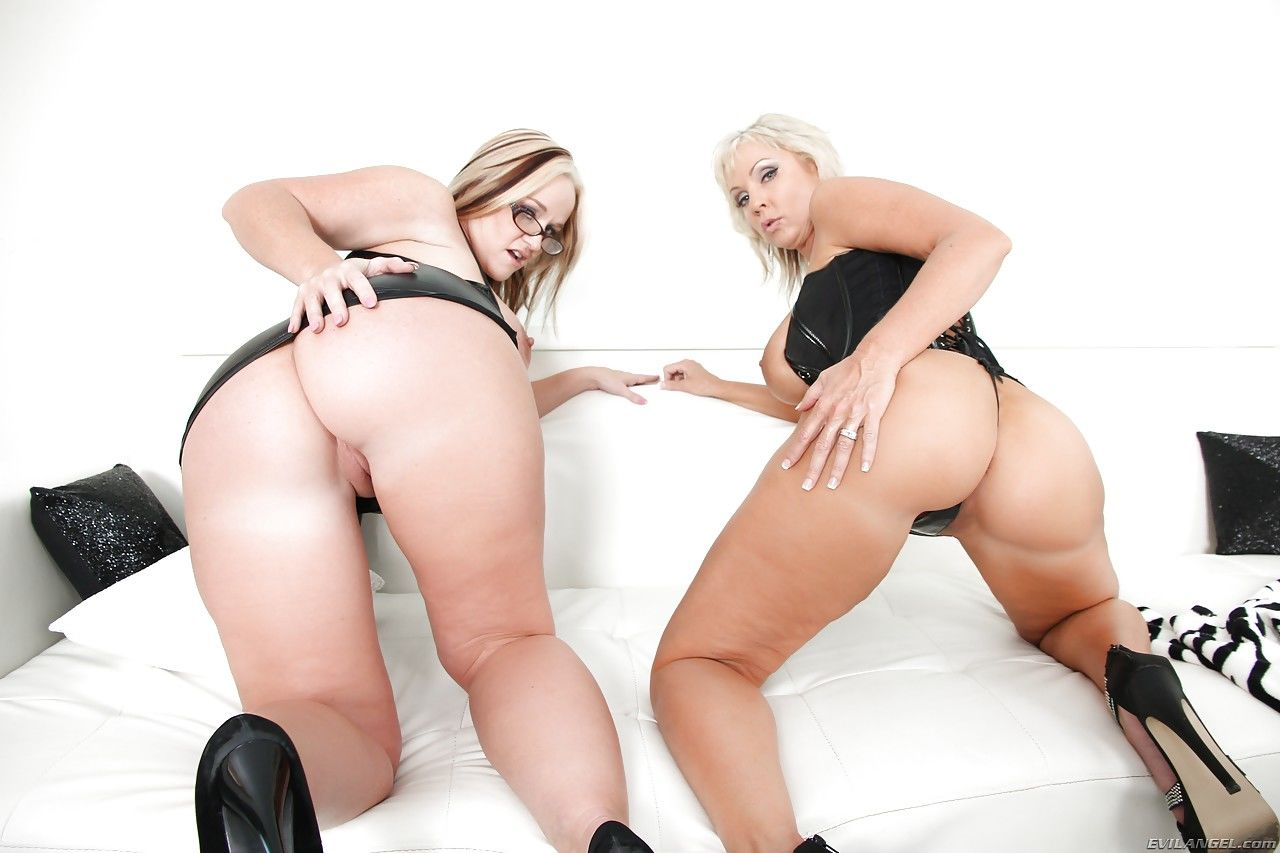 Hot mature Dee Siren & Naughty Alysha in latex on knees baring sexy ass