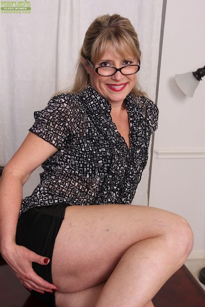 Older lady Rebecca Hill unveiling small tits in glasses and leather skirt