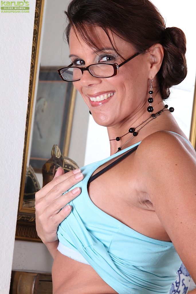 Mature temptress in glasses and nylons undressing and exposing her gash