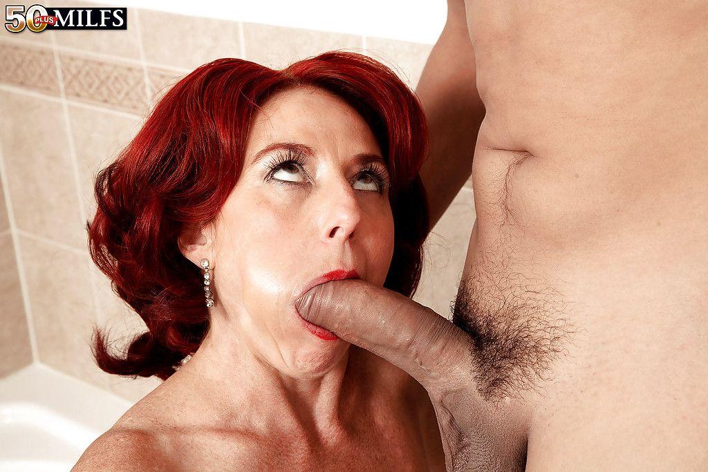 Older flaming redhead Karen Kougar giving large cock a BJ in bathtub