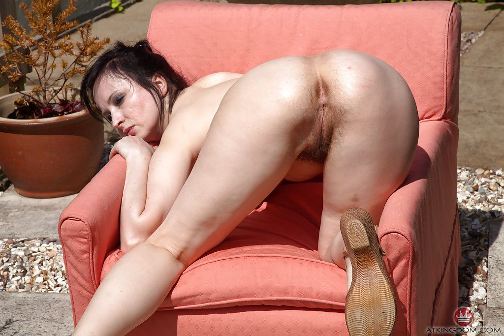Middle aged brunette Nikita showing off her hairy pussy in backyard chair