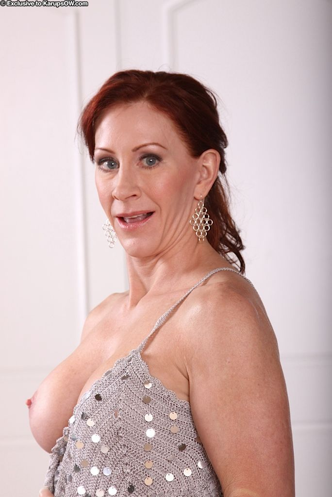 Mature redhead Catherine De Sade stripping off dress and panties to pose naked