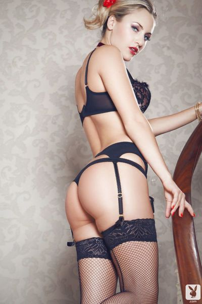 Ravishing centerfold in openwork stockings slipping off her lacy lingerie