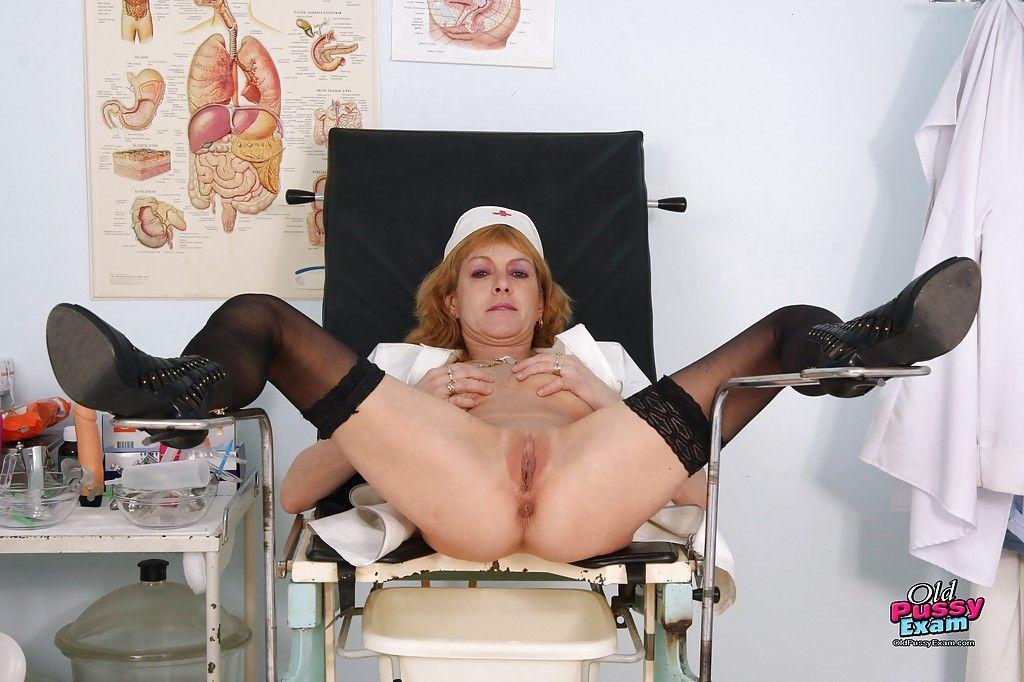 Naughty redhead mature nurse on high heels toying her shaved twat