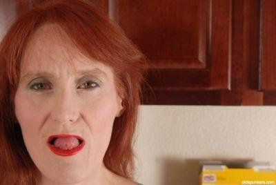 Redhead granny Debra is lying naked on the floor and masturbating