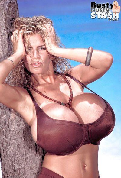 Older big tit model Busty Dusty unleashing huge hooters from bikini on bach