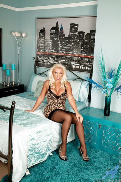 Sassy blonde mature vixen in stockings playing with herself on the bed
