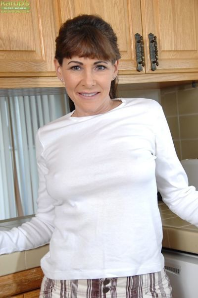 Mature woman Alexandra Silk revealing big tits and pierced cunt in kitchen