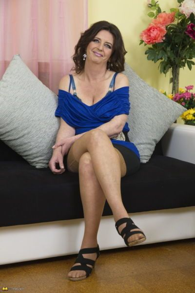 Middle aged lady playfully strips down to lingerie and tan colored stockings