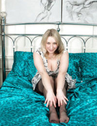 Curvy blonde lady Mel Harper showing off large boobs in nylons on bed