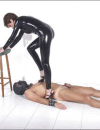 Saucy femdom in latex outfit torturing and stroking off her male pets cock
