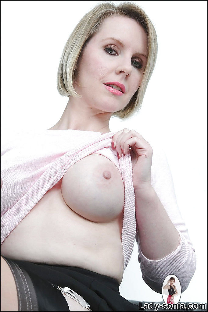 Salacious mature blonde uncovering her round boobs and inviting cunt
