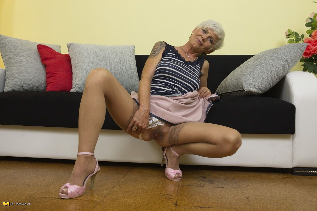 British granny with tattoos strips to tan stockings before pussy play
