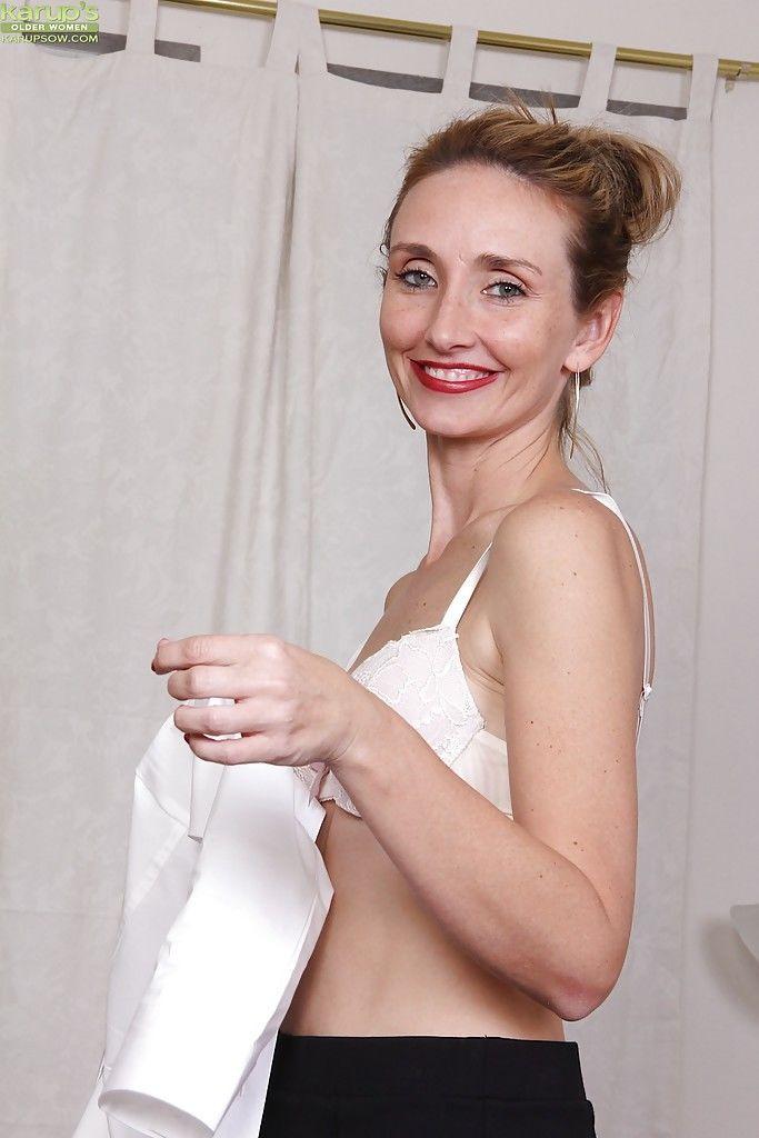 Mature woman Heidi Van Moore modeling naked in her office after disrobing