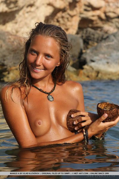 Erotic girl Mango A with perky tits showing off wet shaved pussy on beach