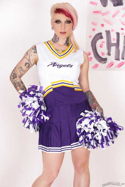 Tattooed chick Scarlet Lavey works free of a cheerleader outfit to pose naked