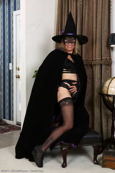 Aged blonde lady Jade Allan doffs a witchs outfit and mask in black stockings