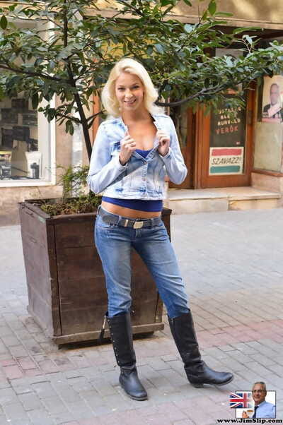 Young blonde in blue jeans and leather boots does a striptease