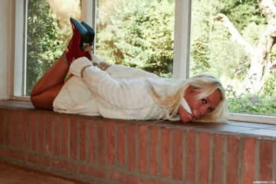 Hogtied and cleave gagged blonde in red high heels Natalie lays by the window