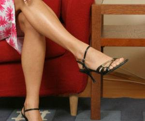 Leggy brunette floosie revealing her goods and licking her..