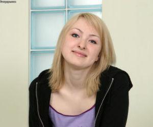 Playful blonde girl in white socks undressing and exposing..